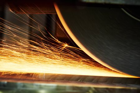 industrial grinding. finishing metal surface on horizontal grinder machine