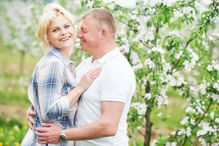 smiling adult couple in love. Blossoming tree garden 免版税图像