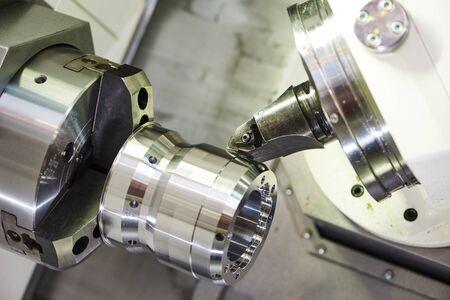 Moderna máquina CNC para trabajar metales con herramienta de corte durante el torneado de detalles en la fábrica. Foto de archivo