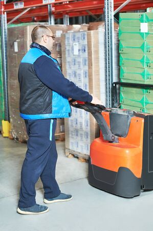 Warehouse worker man with pallet truck stacking cardboxes in storehouse Stock Photo