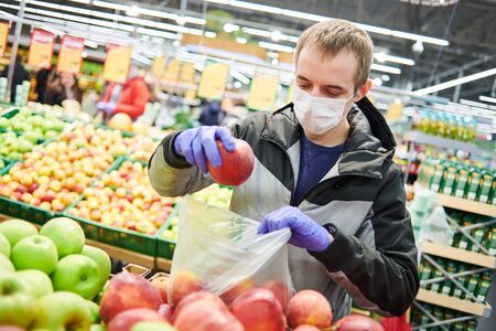 man in mask and protective gloves buying food in shop at coronavirus epidemic Foto de archivo