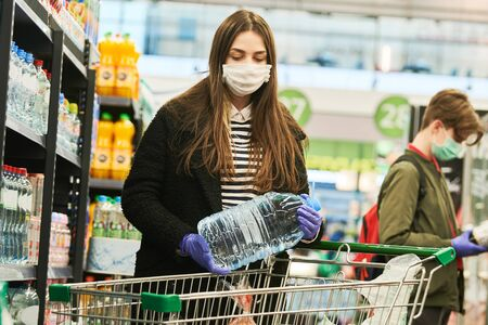 man in mask and protective gloves buying water shop at coronavirus epidemic