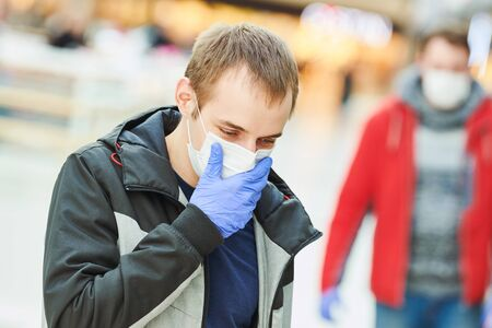 man with face mask coughing at public place. coronavirus outbreak