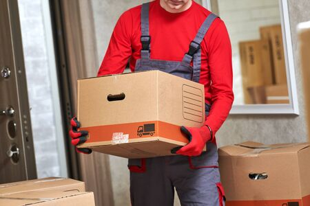 Moving or delivery service. Worker carrying cardboard boxes into home
