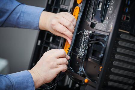 Computer assembling or repair service. Repairman installing cable components during case maintenance