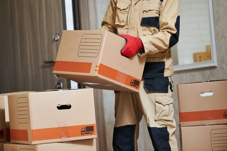 Mover worker in uniform carrying cardboard boxes into home during moving. Delivery or move service Stock Photo