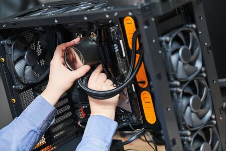 Computer assembling service. Serviceman installing liquid cooling system on processor