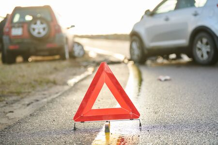 Warning red triangle for car crash accident. Car collision on city street. Two damaged automobiles.