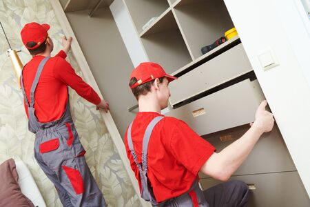 Furniture assembling. Professional Contractor Carpenter worker installing cabinet at living room of new house. Stock Photo