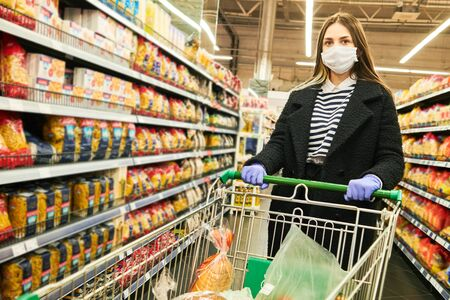 man in mask and protective gloves with cart in shop at coronavirus epidemic Stock Photo