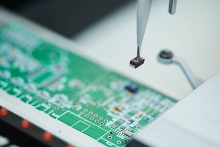 microchip manufacturing. Semi automatic machine robot installing semiconductor chip on board.