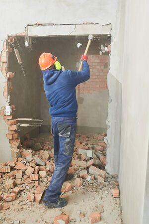 demolition work. Worker builder with sledgehammer destroying interior wall. Rearrangement during renovation. Banco de Imagens
