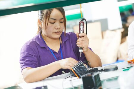 chinese female worker in assembling electronic device on factory