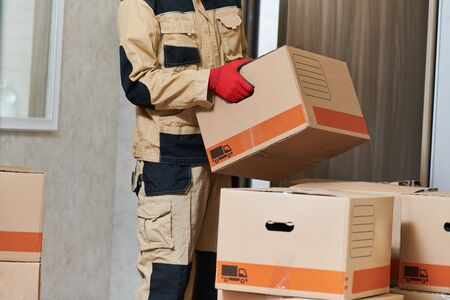 Moving or delivery service. Mover worker carrying cardboard boxes into home Stock Photo