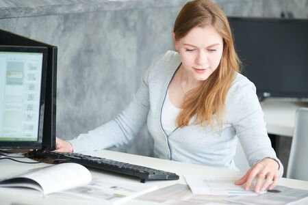 female designer using computer while working with design project Standard-Bild