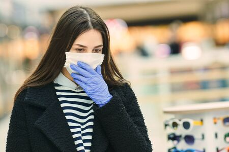 woman with face mask coughing at public place. coronavirus outbreak