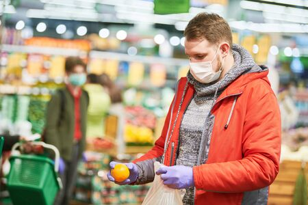 man in mask and protective gloves buying food in shop at coronavirus epidemic Standard-Bild