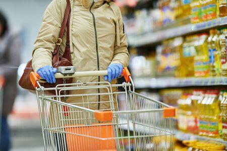 femme faisant ses courses au supermarché alimentaire avec masque et gants de protection lors de l'épidémie de coronavirus covid-19