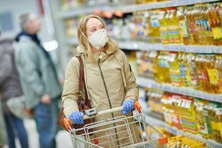Mujer de compras en el supermercado de alimentos con máscara y guantes protectores en el brote de coronavirus covid-19