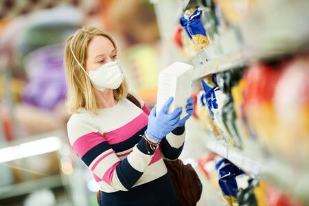 woman shopping at food supermarket in mask and protective gloves at coronavirus covid-19 outbreak
