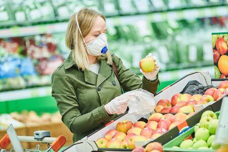 femme en masque et gants de protection achetant de la nourriture en magasin lors d'une épidémie de coronavirus