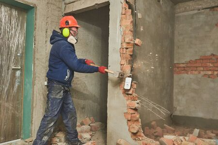 demolition work. Worker builder with sledgehammer destroying interior wall. Rearrangement during renovation. Standard-Bild