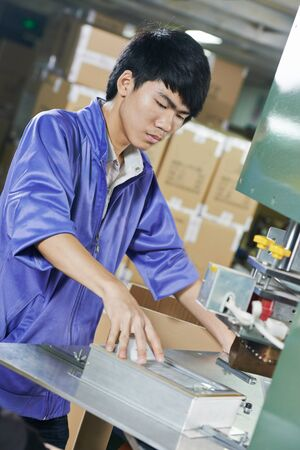 chinese worker operating press at factory