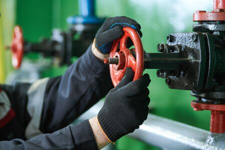 Industrial oil service and mantenance. industrial worker open valve on pipeline at oil factory Standard-Bild