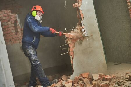 demolition work and rearrangement. worker with sledgehammer destroying wall Standard-Bild