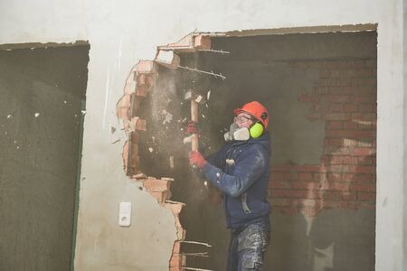 demolition work and rearrangement. worker with sledgehammer destroying wall Banco de Imagens