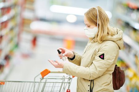 woman uses antibacterial sanitizer sprayer while shopping at food supermarket at coronavirus covid-19 outbreak Stock Photo