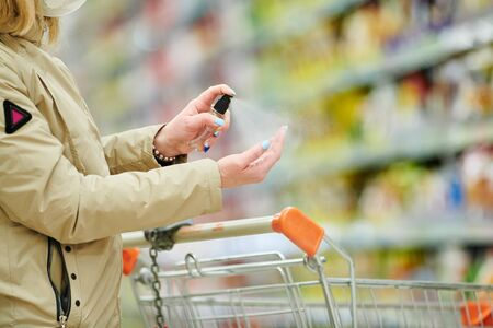 woman shopping at food supermarket in mask and protective gloves at coronavirus covid-19 outbreak Stockfoto
