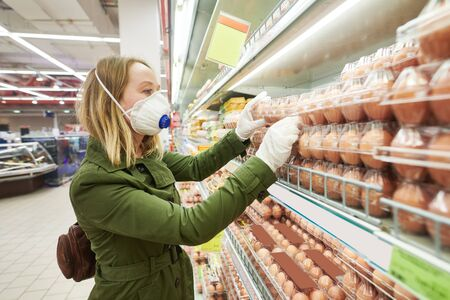 woman shopping egg food supermarket in mask and protective gloves at coronavirus covid-19 outbreak