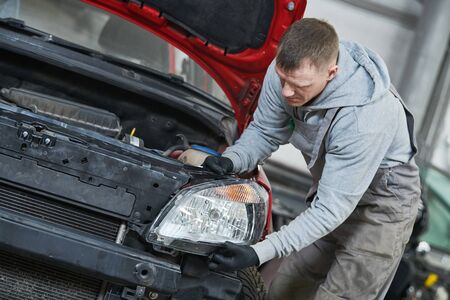 Auto service garage shop. Worker mechanician assembling headlight lamp of automobile car. Body repair or replacement