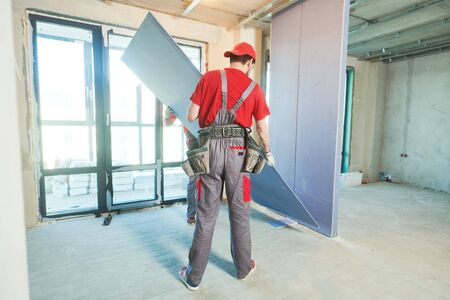 Gypsum plasterboard work. Drywall construction at home. Contractor worker installing wall Standard-Bild