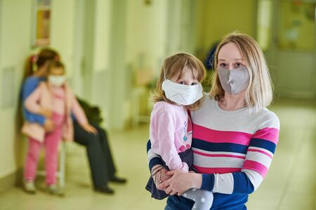 woman and child in protective mask waiting doctor in hospital clinic hall at coronavirus epidemic