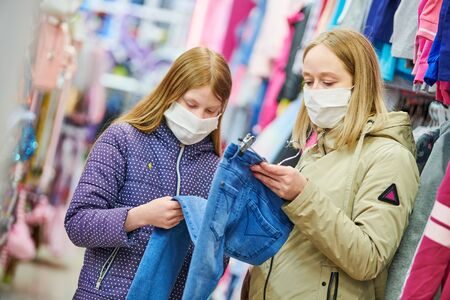 woman and girl in protective mask shopping clothing jeans pants in apparel shop at coronavirus epidemic