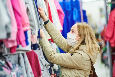 woman in protective mask shopping clothing in apparel shop at coronavirus epidemic