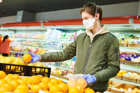 man in mask and protective gloves buying food in shop at coronavirus epidemic Фото со стока