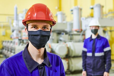 industrial worker portrait in mask at power energy supply factory