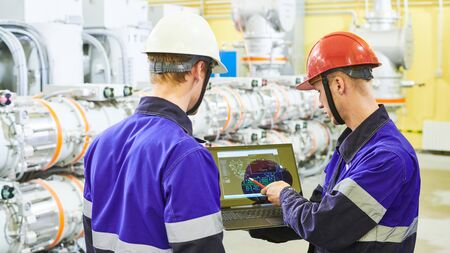 industrial workers with tablet computer at power energy supply factory