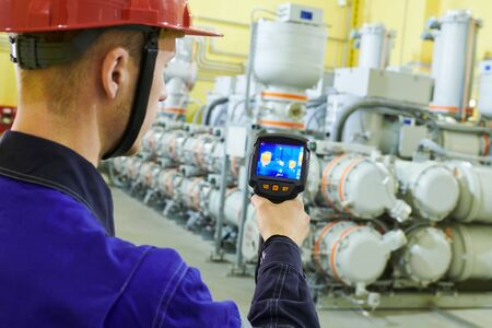 electrician use thermal imaging camera for temperature inspection of industrial indoor electricity substantion high-voltage insulator