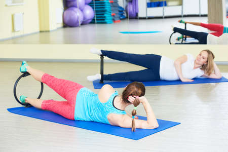 pregnant woman doing fitness exercise with coach