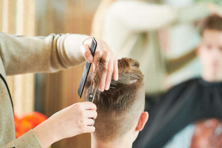 Haircut of young man. Hairdressing at barber shop Imagens
