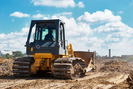 Buldozer moving earth. Road construction building work