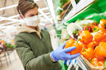 man in mask and protective gloves buying food in shop at coronavirus epidemic Stock Photo