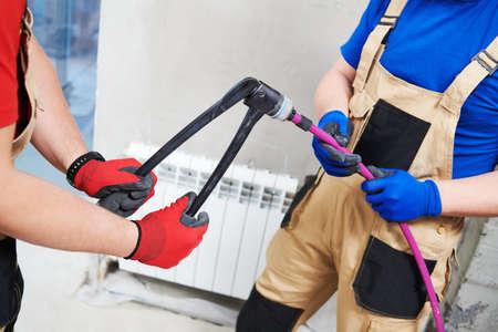 Plumber Installing water heating radiator Stock Photo