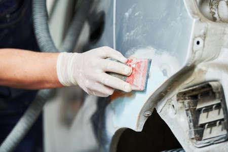 Auto repairman plastering and sanding  bonnet