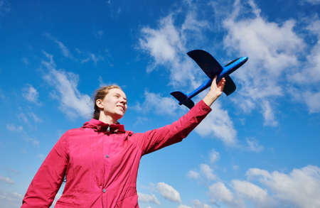 Girl playing with airplane. blue sky background. Travel and vacation concept Zdjęcie Seryjne