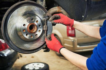 Automobile brake pads replacement in car repair shop or garage